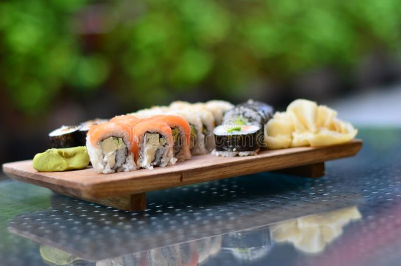 Delicious assorted sushi on a white plate on a green background stock photos