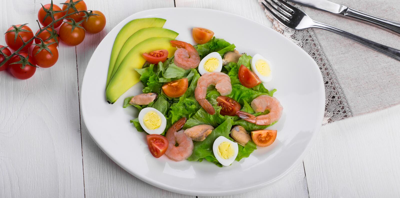 Delicious appetizing vegetable salad with seafood on a white plate. stock photos