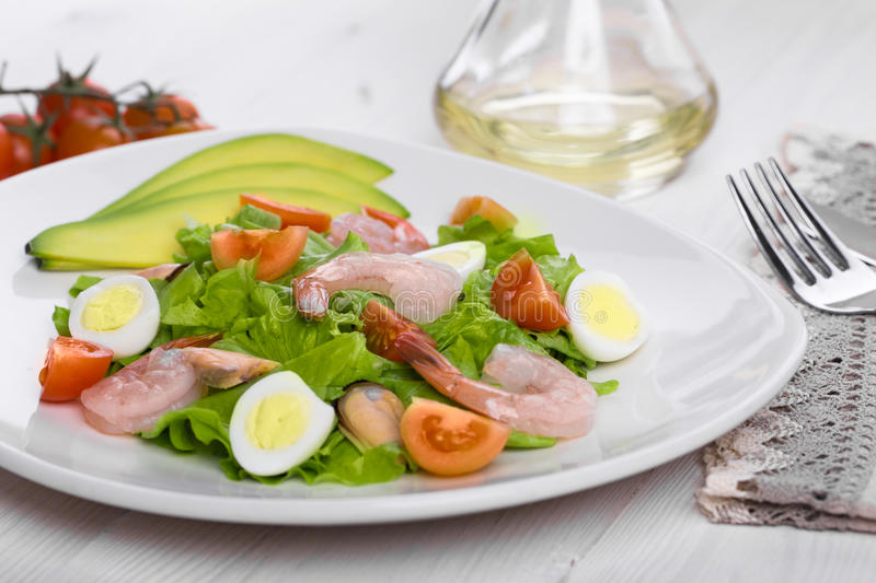 Delicious appetizing vegetable salad with seafood on a white plate. royalty free stock photo