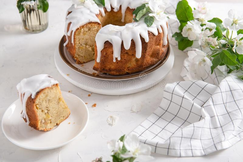 Delicious apple cake with cinnamon and icing on white background with flowering apple branches. Spring mood. Copy space. Bakery, stock photography