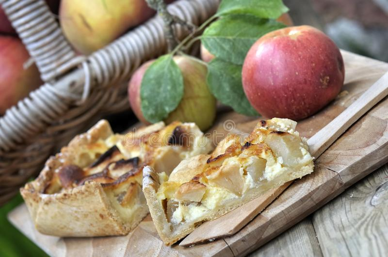 Delicious apple pie. Slice of apple pie with red apples on wooden background royalty free stock photography