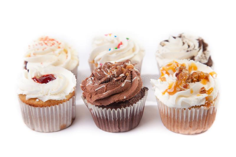 Delicious assorted cupcakes. With different toppings and flavor in white background stock photography