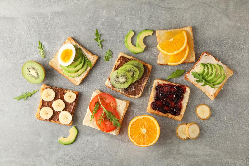 Delicious assorted sandwiches on grey background stock image
