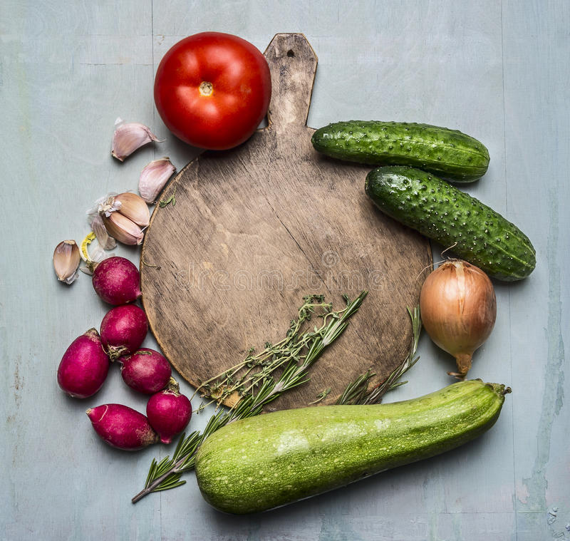 Delicious assortment of farm fresh vegetables around a round cutting board place text,frame on wooden rustic background top vi stock images