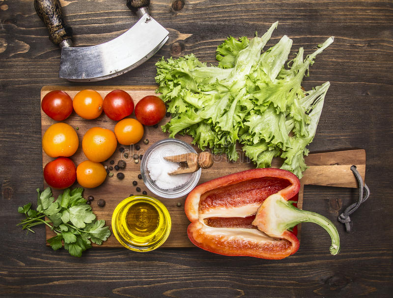 Delicious assortment of farm fresh vegetables on a cutting board wooden rustic background top view close up. Delicious assortment of farm fresh vegetables on a stock photos