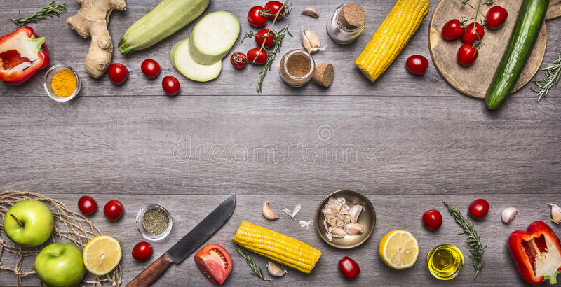Delicious assortment of farm fresh vegetables with knife on grey wooden background , top view. Vegetarian ingredients for cooking. Delicious assortment of farm royalty free stock photography