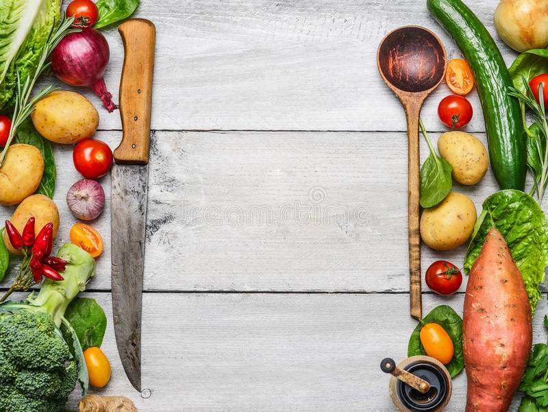 Delicious assortment of farm fresh vegetables with knife and spoon on white wooden background, top view. Vegetarian ingredients fo royalty free stock images