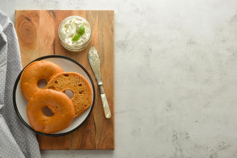 Delicious bagels with cream cheese on wooden board, pastry bread for breakfast. Top view. Copy space stock photos