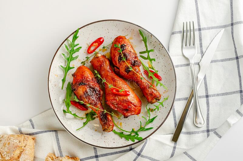 Delicious baked chicken drumsticks or legs with paprica, chili pepper, arugula and thyme on white background. Top view. Flat lay stock photo