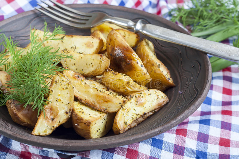Delicious baked fried potatoes with dill in white plate on table. Closeup royalty free stock photos