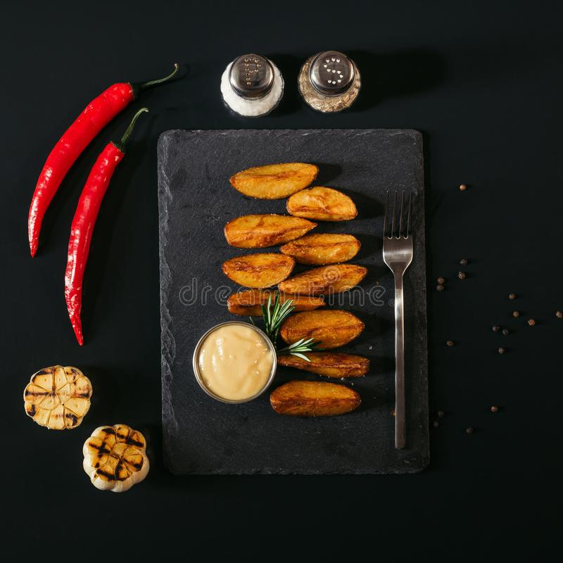 Delicious baked potatoes with sauce and fork on slate board and spices with garlic and chili peppers. On black stock images