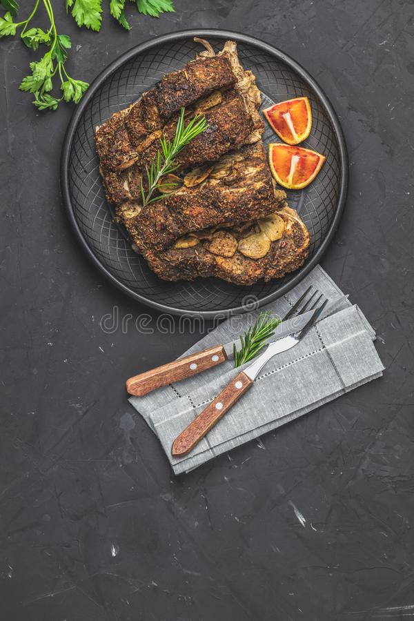 Delicious baked roast pork meat in black ceramic plate. With garlic and spices. Dish for dinner. Top view, flat lay, dark concrete surface, copy space for you stock images