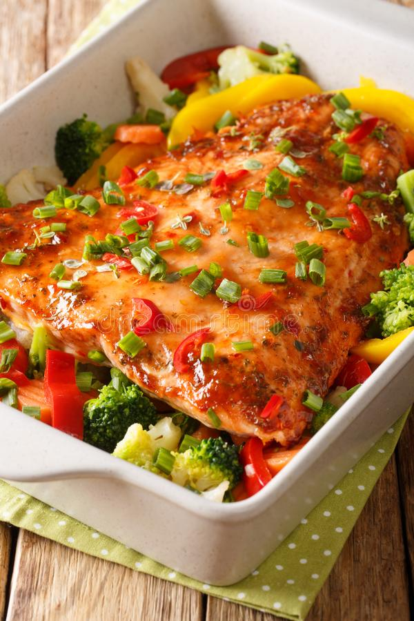 Delicious baked salmon fillet with vegetables close-up in a baking dish. vertical royalty free stock photo