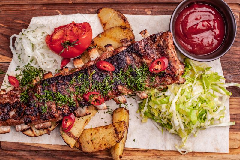 Delicious barbecued ribs seasoned with fresh herbs, cabbage salad, backed potato on an old rustic wooden chopping board stock photo