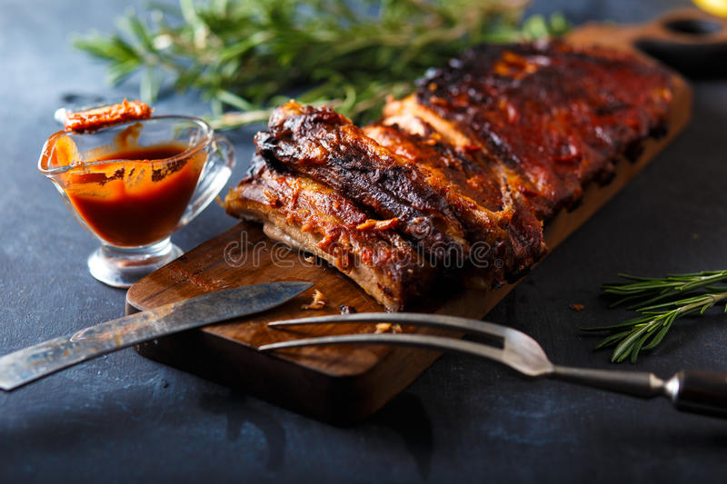 Delicious barbecued ribs seasoned with a spicy basting sauce and served with chopped stock photo
