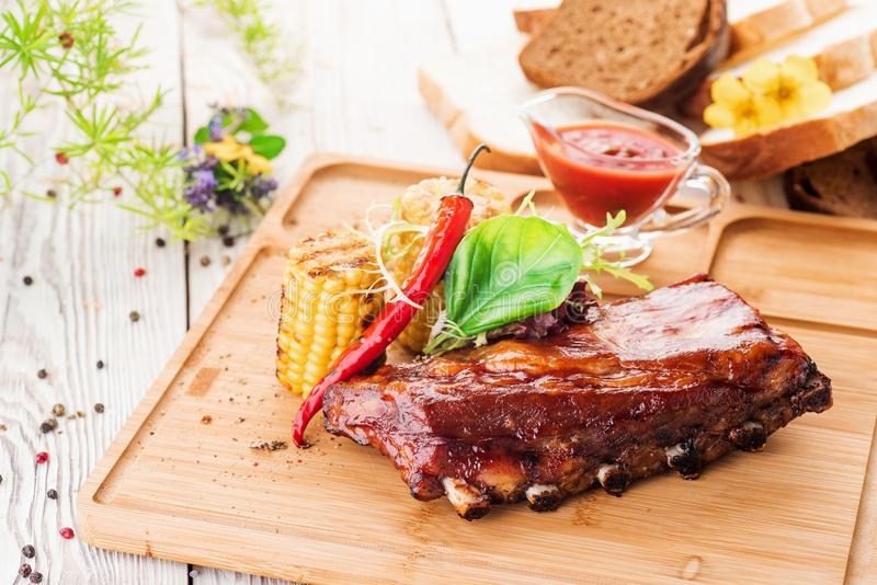 Delicious barbecued ribs seasoned with a spicy basting sauce and served with salad and grilled corn on an wooden board. close up stock photos