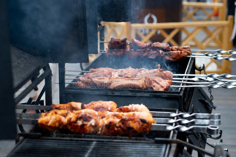 Delicious bbq kebab grilling on open grill, outdoor kitchen. food festival in city. tasty food roasting on skewers, food-court. Description: delicious bbq kebab royalty free stock photo