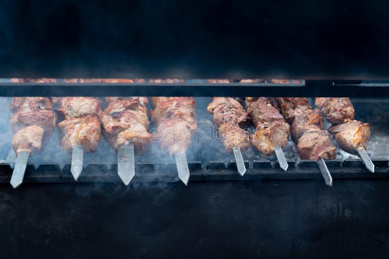 Delicious bbq kebab grilling on open grill, outdoor kitchen. food festival in city. tasty food roasting on skewers, food-court. Description: delicious bbq kebab royalty free stock photos