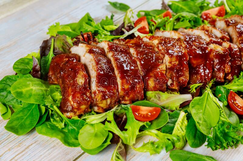 Delicious BBQ pork ribs with green salad and tangy BBQ sauce stock image