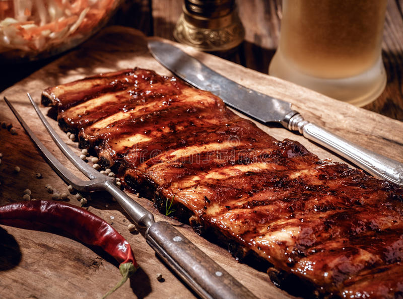 Delicious BBQ ribs with coleslaw and beer on wooden table.  stock photography