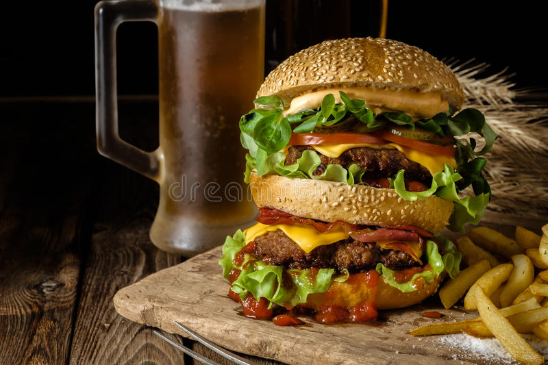 Delicious beef burger with chips and beer on wooden table. Delicious beef burger with chips and beer on wooden table stock photography