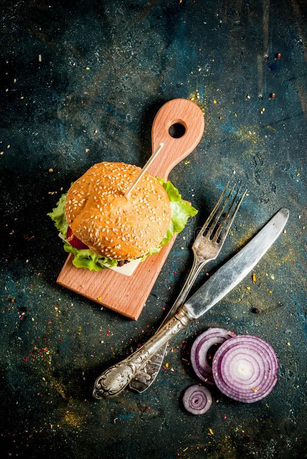 Delicious beef and cheese burgers. On dark table stock images