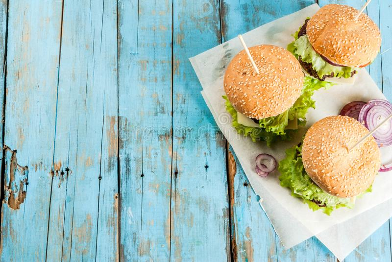 Delicious beef and cheese burgers. Picnic, Fast food. Unhealthy food. Delicious Fresh Tasty Burgers with Beef Cutlet, fresh Vegetables and Cheese on old rustic royalty free stock image