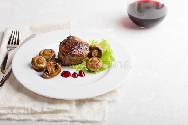 Beef filet mignon with roasted mushrooms. Delicious beef filet mignon served on white plate with roasted mushrooms royalty free stock photos