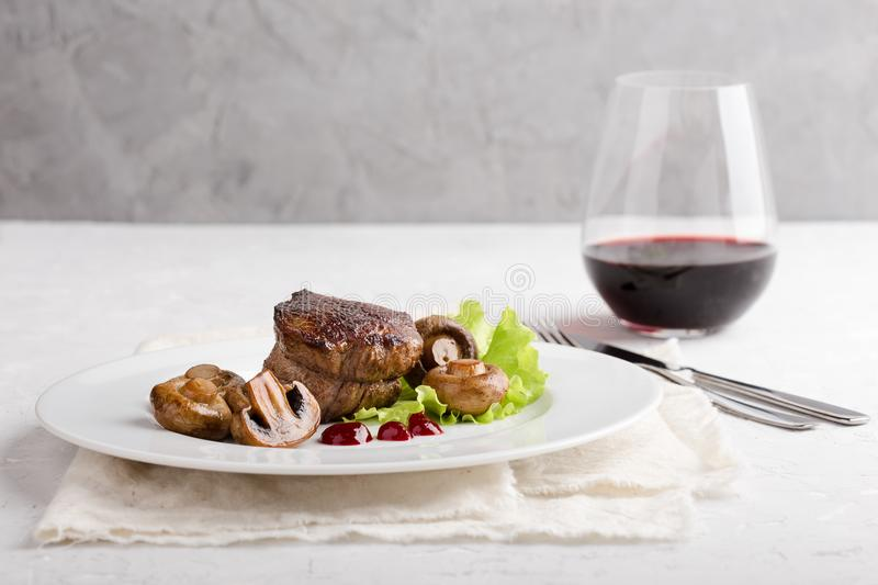 Beef filet mignon with roasted mushrooms. Delicious beef filet mignon served on white plate with roasted mushrooms royalty free stock photo