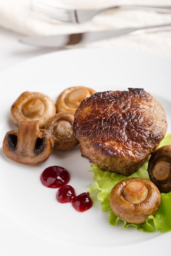 Beef filet mignon with roasted mushrooms. Delicious beef filet mignon served on white plate with roasted mushrooms stock photo