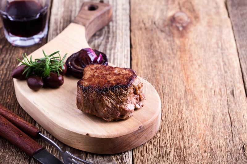 Delicious beef filet mignon. Served on wooden cutting board with roasted red onion and rosemary royalty free stock photo