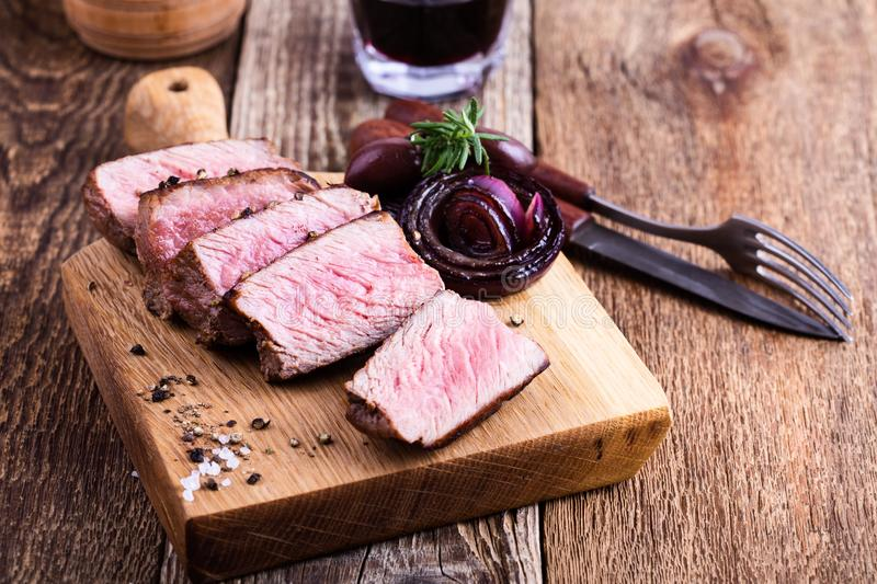 Delicious beef filet mignon. Served on wooden cutting board with roasted red onion and rosemary royalty free stock images