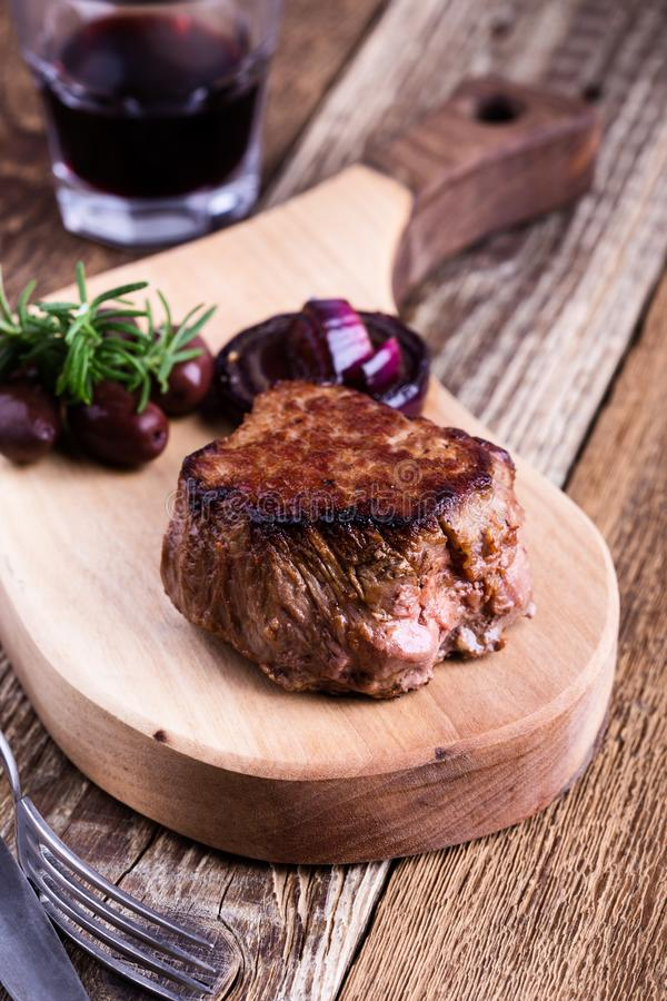 Delicious beef filet mignon. Served on wooden cutting board with roasted red onion and rosemary royalty free stock photography