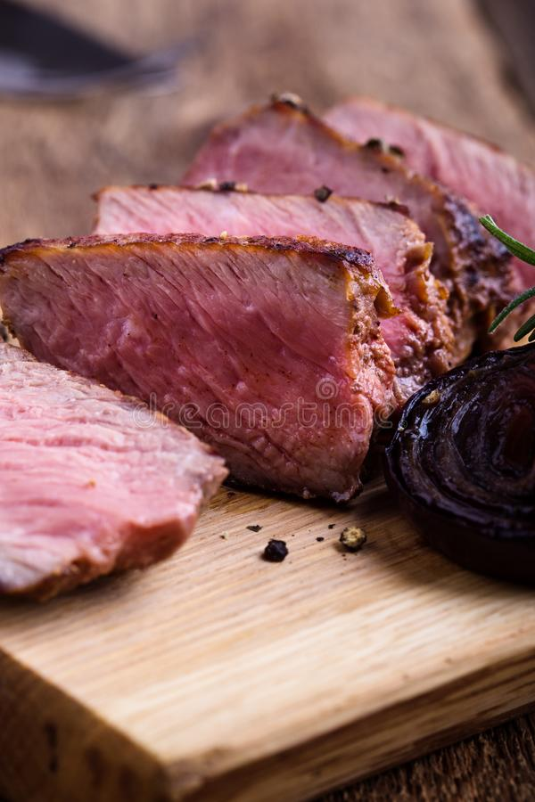 Delicious beef filet mignon. Served on wooden cutting board with roasted red onion and rosemary stock photography