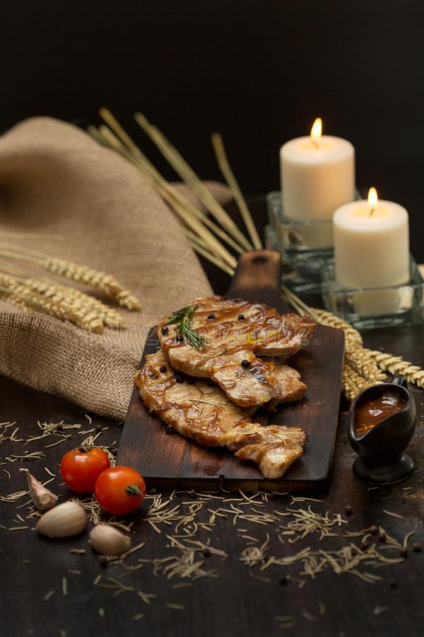 Delicious beef or pock steaks on wooden table. Grilled bbq steak stock photography