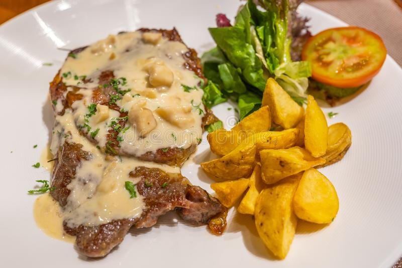 Savory beef steak with creamy mushroom sauce and vegetables royalty free stock photo
