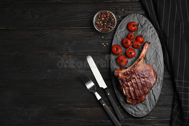 Delicious beef steak served on black wooden table, flat lay. Space for text stock photo