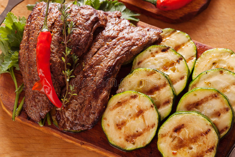 Delicious beef steak with vegetable over wooden table royalty free stock photos