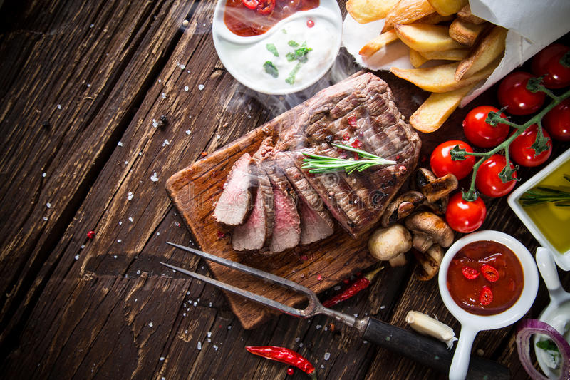 Delicious beef steak. On wooden table stock photography