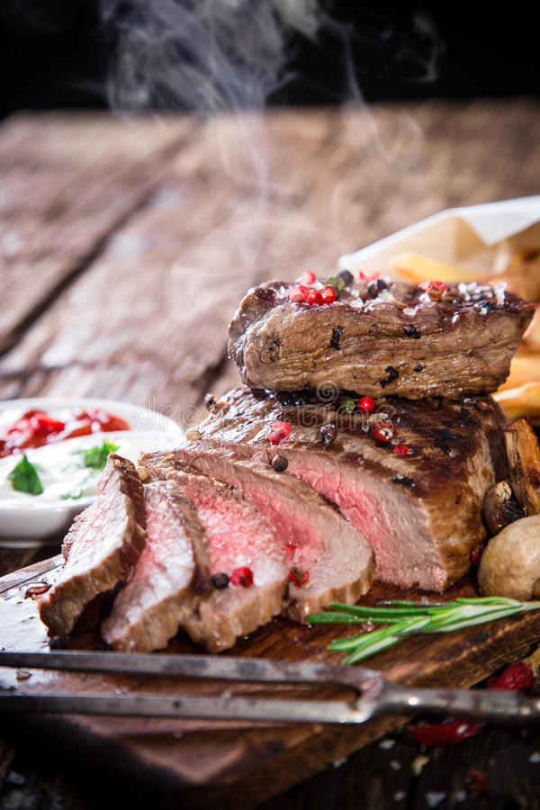 Delicious beef steak. On wooden table stock images