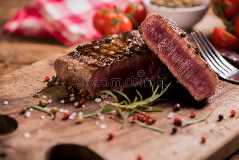 Delicious beef steak on wooden table stock photography