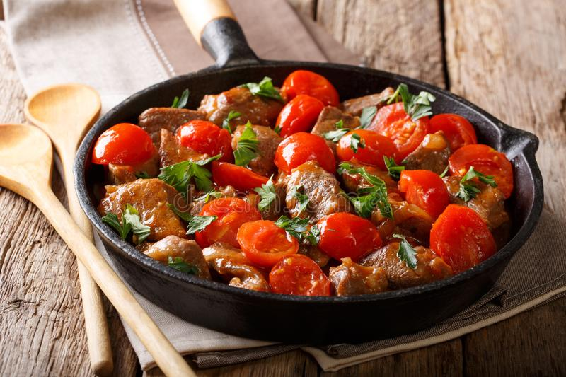 Delicious beef stew with tomatoes and greens close-up in a frying pan. horizontal royalty free stock photography