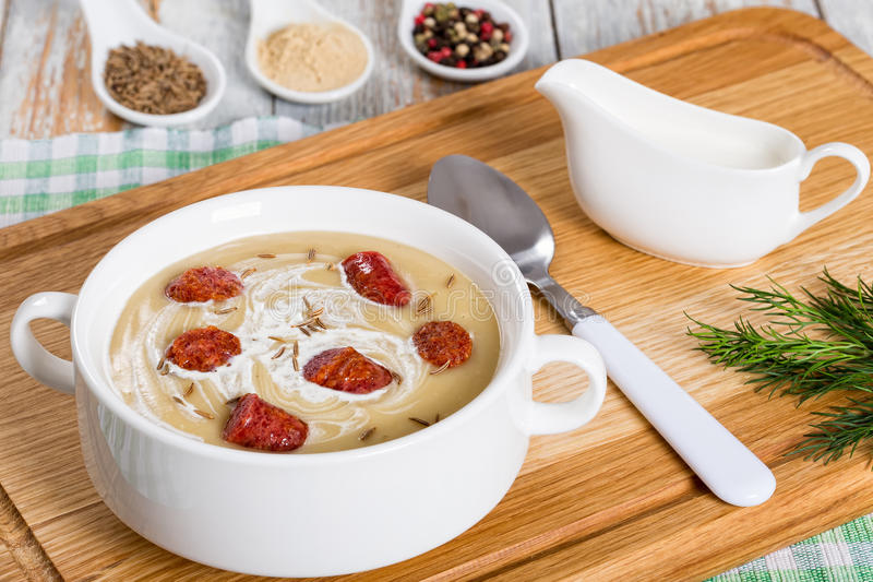 Delicious Beer and cream spicy Soup with Kielbasa Sausage. Sprinkled with caraway in white soup cup on chopping board, spices on background, authentic recipe stock photos
