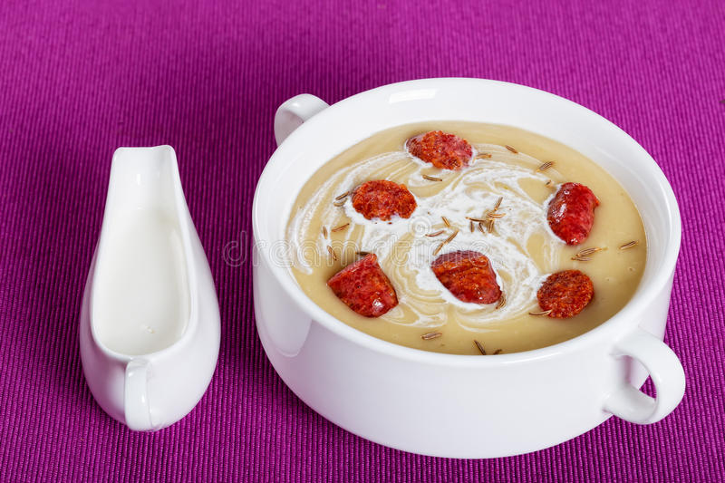 Delicious Beer and cream spicy Soup with Kielbasa Sausage. Sprinkled with cumin in white soup cup on magenta table mat with cream in gravy boat, authentic stock photography