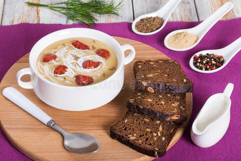 Delicious Beer and cream spicy Soup with Kielbasa Sausage. Sprinkled with cumin in white soup cup on round board with rye bread, authentic recipe, close-up stock image