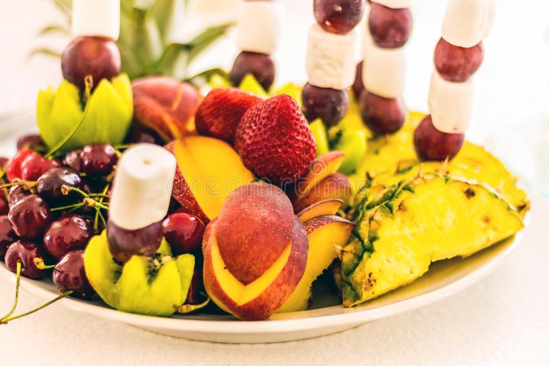 Delicious berries and fruits on a platter. Strawberries, cherrie. S, peaches, mangoes, kiwi for a festive table royalty free stock images
