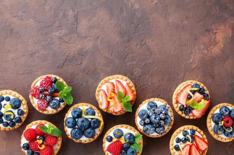 Delicious berry tartlets or cake with cream cheese decorated lemon peel and mint leaf from above. Tasty pastry desserts. royalty free stock photo