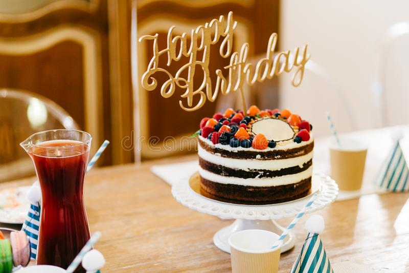 Delicious birtday cake on wooden table with glasses and compote. Birtday table. Preparation and celebration concept. Portrait of b. Irthday party supplies. Table royalty free stock image