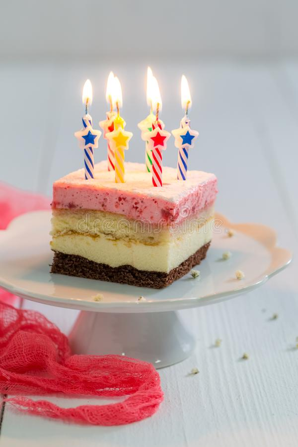 Delicious birthday cake with burning candles on wooden table royalty free stock images