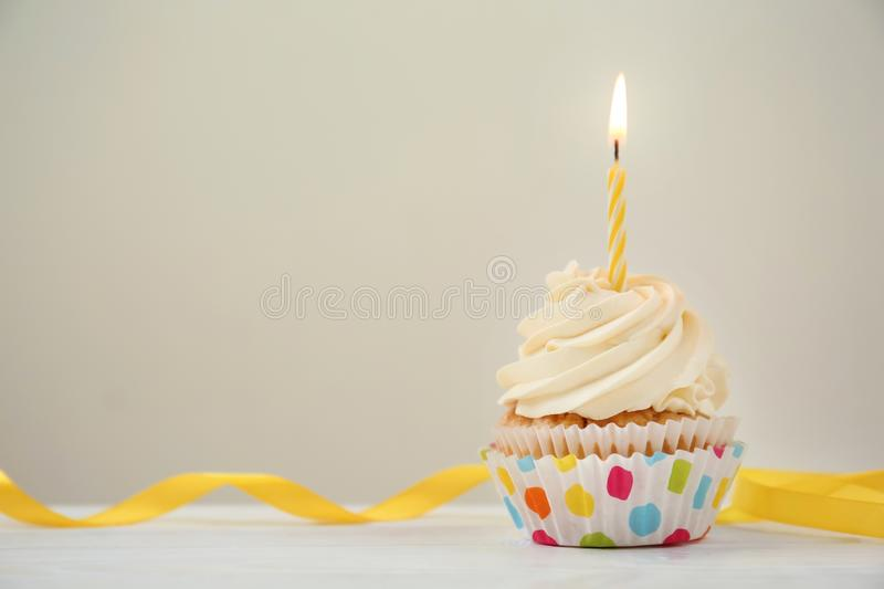 Delicious birthday cupcake with burning candle on white wooden table stock photos